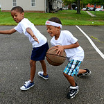 Ray Smith, 7, and Aarion Chambers, 6, play basketball on Kid's Day at the Lorain Metropolitan Housing Authority on July 19.   KRISTIN BAUER | CHRONICLE