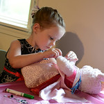Samantha Capel, 4, of Cleveland dresses her bear at Schoepfle Garden during a tea party on July 26.  KRISTIN BAUER | CHRONICLE