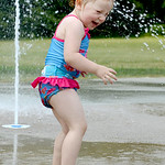 Ava Coker, 2, of Grafton, reacts when one of the North Park Splash Pad jets splashes her on July 22.  KRISTIN BAUER | CHRONICLE