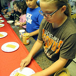 "Lyndsey Harpst, right, of Elyria, spreads peanut butter on a graham cracker to pass on to Gage Cohoon, of Amherst, in an assembly line at the ""History Through Young Eyes"" program at Amherst  …"