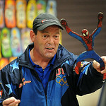 Gary Broadbent, of Canton, formerly of North Ridgeville, shows a spiderman boomerang during a demonstration for kids at the Lorain Public Library Main Branch on July 28.  Broadbent has over  …