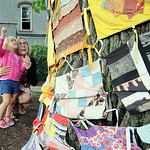 Caitlin Mathaes, 4, with her mother Jessica, of Austin, Texas, looks up at her favorite quilt at an outside exhibition of the 'Artist As Quiltmaker' at New Union Center for the Arts in Oberl …