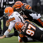 Cleveland Browns quarterback Colt McCoy (12) is sacked by Cincinnati Bengals defensive end Carlos Dunlap (96) and defensive tackle Geno Atkins (97) in the second half of an NFL football game …