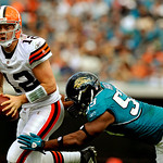 Cleveland Browns quarterback Colt McCoy (12) scrambles out of the pocket while chased by Jacksonville Jaguars defensive end Larry Hart (59) during the first half of an NFL football game, Sun …