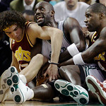 Boston Celtics forward Kevin Garnett, center, is flanked by Cleveland Cavaliers center Anderson Varejao, left, of Brazil, and forward Antawn Jamison as he hangs on to a loose ball during the …