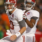 Alabama quarterback AJ McCarron (10) congratulates Amari Cooper after Cooper's touchdown reception during the second half of the BCS National Championship college football game against Notre …