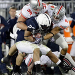 Ohio State's Austin Spitler (38) and Kurt Coleman (4) tie up Penn State running back Evan Royster (22) during the second half of an NCAA college football game in State College, Pa., Saturday …