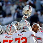 Ohio State cornerback Anderson Russell, facing the camera, holds up his helmet as he gathers with his teammates before an NCAA college football game against Penn State in State College, Pa., …