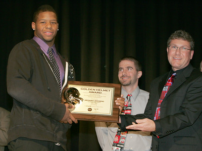 2DEC09  Anthony Hitchens receives the Golden Helmet Award from Gregory Finton, Territory Development Manager with the Coca Cola Bottling C o. on Lake Ave.  In the center is Franco Gallo, Athletic Director and Assistant Principal at Clearview H.S.  photo by Chuck Humel