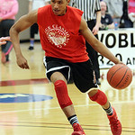 ANNA NORRIS/CHRONICLE Elyria's Isaiah Walton drives the ball towards the basket against the West team in the Lorain County Boys Legeza Cage Classic all-star game at Oberlin College Sunday ni …
