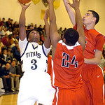 Lorain's Demon Hisle shoots past Elyria's A.J. Johnson and Jarred Schultz. LINDA MURPHY/CHRONICLE