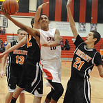 Elyria's Isaiah Walton goes to the hoop between Normandy's Donny Campbell, left, and Ken Kitko. STEVE MANHEIM/CHRONICLE