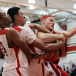 ANNA NORRIS/CHRONICLE Elyria's Isaiah Walton, middle, and Parma's Tyler Deutsch battle for possession of the rebound in the second quarter Friday night at Elyria High School.