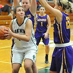 Elyria Catholic's Jessie Lee is defended while going up for shot by Lakewood's Erin Hoffert, right, and Madison Clause. STEVE MANHEIM/CHRONICLE