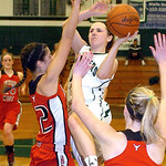 Elyria Catholic's Riley Schill drives to the basket Saturday against the defense of Lutheran West's Katelyn Thornton, left, and Kimmy Evans. LINDA MURPHY/CHRONICLE