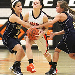 ANNA NORRIS/CHRONICLE North Olmsted's Hayley Hicks drives between Olmsted Falls' Melissa Holcomb (24) and Madison Craft (33) in the first half Saturday afternoon at North Olmsted High School …