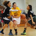 Firelands High School senior Casey Morrissette (10) takes the ball towards the hoop as Lorain High School senior Destiny Wilson (20) and Amherst High School senior Sher Champe (3) attempt to …
