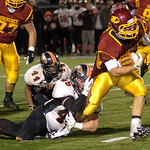 Avon Lake's Wyatt Ohm digs for more yardage as North Olmsted's Chris Lewis hangs on to try to stop him. LINDA MURPHY/CHRONICLE