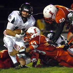 Medina's Jerry Klue is stopped by Elyria's Connor Kamczyc,Jumarr Lewis and Lonzell Cash. LINDA MURPHY/CHRONICLE