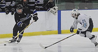 Midview's Zach Schneider moves down ice from Benedictine's Clayton Hongash. STEVE MANHEIM/CHRONICLE