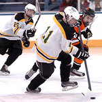 Amherst's #11 Kevin Burgett works the puck past North Olmsted's #21 Shawn Elliott.