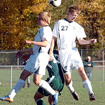Amherst's No. 6 Garett Klekota and No. 27 Jake McDonald squeeze Strongsville's No. 13 Bryan Wolanski out as they head the ball.