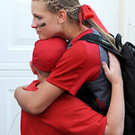 Elyria High School left fielder Anna Daly hugs Levi Ellis, 9, after a loss against Grove City.  KRISTIN BAUER | CHRONICLE