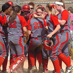 Elyria's #25 Holly Howser is greeted by teammates as she reaches home plate after hitting a home run.