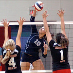 Lorain's #10 Kayla Lurry tries to spike the ball past Brookside's #4 Tyller Holley and #1 Celina Rock.