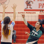 Elyria Catholic's Jessie Lee hits over Independence's Meredith Collins. STEVE MANHEIM/CHRONICLE