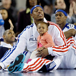 East All-Star Paul Pierce of the Boston Celtics holds his daughter, Prianna Lee, as he watches the second half of the NBA All-Star basketball game with his Celtics teammate Rajon Rondo, righ …