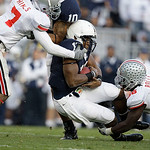 Penn State quarterback Daryl Clark, center, is tackled by Ohio State's Jermale Hines (7) and Brian Rolle during the first half of an NCAA college football game in State College, Pa., Saturda …