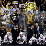 Boston Bruins fans cheer behind the Chicago Blackhawks bench during the third period in Game 3 of the NHL hockey Stanley Cup Finals in Boston, Monday, June 17, 2013. (AP Photo/Charles Krupa)