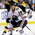 Chicago Blackhawks center Marcus Kruger (16) moves the puck in front of Boston Bruins left wing Milan Lucic, rear, during the first period in Game 3 of the NHL hockey Stanley Cup Finals in B …
