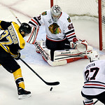 Boston Bruins center Patrice Bergeron (37) moves the puck between Chicago Blackhawks goalie Corey Crawford (50) and defenseman Johnny Oduya (27), of Sweden, during the first period in Game 3 …
