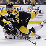 Chicago Blackhawks defenseman Niklas Hjalmarsson, bottom, of Sweden, takes down Boston Bruins left wing Daniel Paille (20) during the second period in Game 3 of the NHL hockey Stanley Cup Fi …
