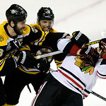 Boston Bruins defenseman Zdeno Chara (33), of Slovakia,  and Boston Bruins defenseman Dennis Seidenberg, center, of Germany, take down Chicago Blackhawks left wing Bryan Bickell, right, duri …