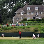 Tiger Woods attempts a putt on the 11th hole green as spectators watch from a property above during the final day of the U.S. Open Sunday Sunday, June 16, 2013 at the Merion Golf Club in Ard …
