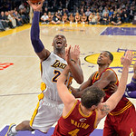 Los Angeles Lakers guard Kobe Bryant, left, goes up for a shot as Cleveland Cavaliers forward Luke Walton, center, falls and forward Tristan Thompson defends during the second half of their  …