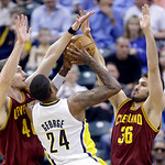 Cleveland Cavaliers center Tyler Zeller, left, and forward Omri Casspi, right, team up to block the shot of Indiana Pacers forward Paul George in the first half of an NBA basketball game in  …