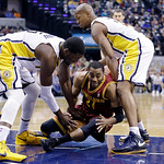 Cleveland Cavaliers guard Wayne Ellington, center, hits the floor for a loose ball between Indiana Pacers center Roy Hibbert, left, and forward David West in the first half of an NBA basketb …