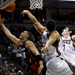 Cleveland Cavaliers' Anthony Parker (18) is fouled as he goes up for a shot against Milwaukee Bucks' Dan Gadzuric (50) and Ersan Ilyasova (7) during the first half of an NBA basketball game  …