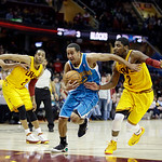 New Orleans Hornets' Brian Roberts, center, drives between Cleveland Cavaliers' Kyrie Irving (2) and Wayne Ellington, left, in an NBA basketball game Wednesday, Feb. 20, 2013, in Cleveland.  …