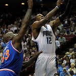 Orlando Magic center Dwight Howard, right, puts up a shot in front of Cleveland Cavaliers center Shaquille O'Neal, left, during the first half of an NBA basketball game in Orlando, Fla., Sun …