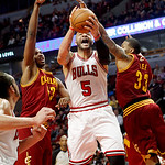 Chicago Bulls' Carlos Boozer (5) shoots between Cleveland Cavaliers' Alonzo Gee (33) and Tristan Thomas during their NBA basketball game, Tuesday, Feb. 26, 2013, in Chicago. The Cavaliers wo …