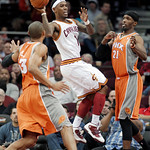 Cleveland Cavaliers' Daniel Gibson, center, looks for help from teammates under pressure from Phoenix Suns' Hakim Warrick, right, and Grant Hill in the fourth quarter in an NBA basketball ga …
