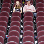 Cleveland Cavaliers fans Emily Loomis, 15, and her father, Dave Loomis, sit in an empty section after the Cavaliers' 120-88 loss to the Boston Celtics in Game 5 of a second round NBA basketb …