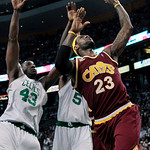 Cleveland Cavaliers forward LeBron James (23) shoots with his left hand against Boston Celtics center Kendrick Perkins (43) and forward Kevin Garnett (5) during the first half of Game 4 in a …