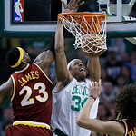 Boston Celtics forward Paul Pierce, center, dunks as Cleveland Cavaliers forward LeBron James, left, and center Anderson Varejao of Brazil, right, watch during the second half of Game 4 in a …