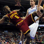 Cleveland Cavaliers' C.J. Miles (0) falls in front of Philadelphia 76ers' Spencer Hawes (00) after he tipped the ball into the basket during the second half of an NBA basketball game on Sund …